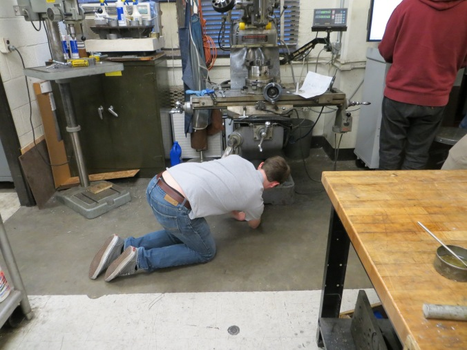 Elliot of LPRD rocketry looking under a bridgeport for a lost screw while machining
