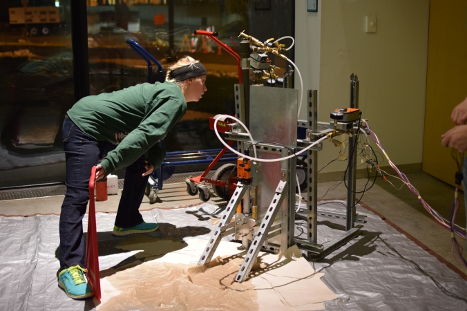 Anna Koene examing LPRD Rocketry rocket test stand control valves and pressure during cold throttle test in TeslaWorks showcase