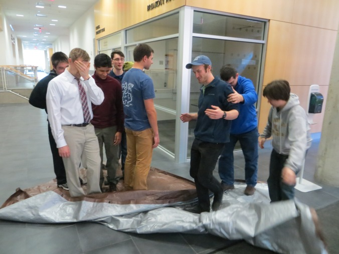 LPRD ROcketry team members attempt to flip a tarp while standing on it team challenge